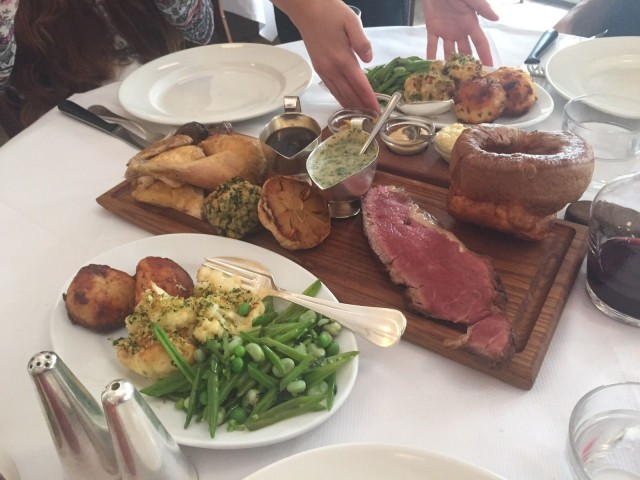 The two meat roasts served on a board with all the trimmings