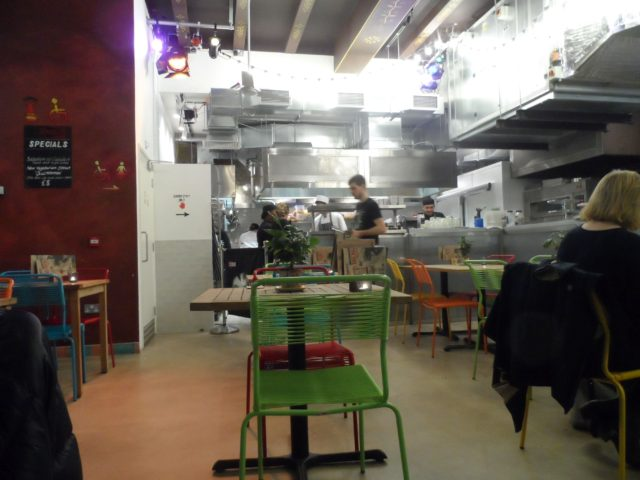 Part of restaurant area showing open kitchen at the back