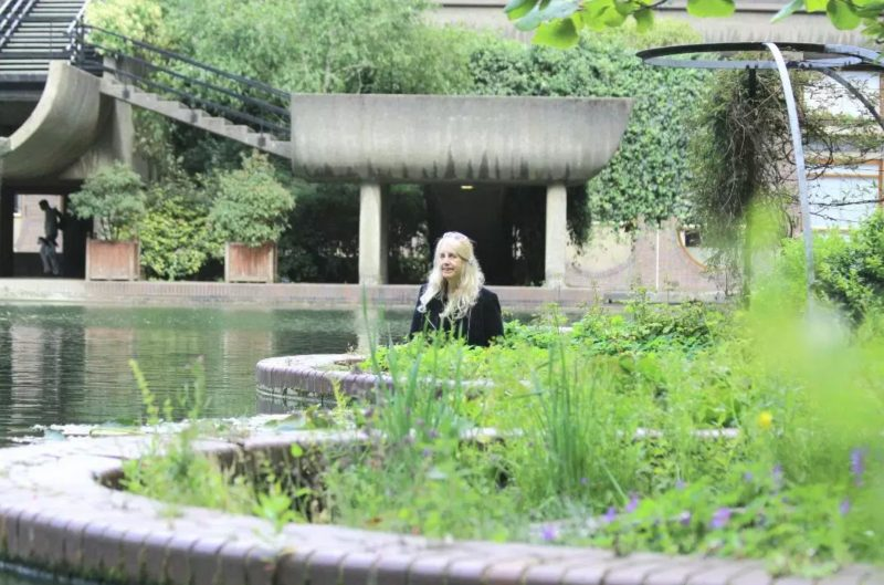 Colour photo. Natasha Anne Kelleher pictured (centre) in the Barbican sunken gardens, with the Brutalist architecture of the waterfall behind her, greenery and flowers in front of her.